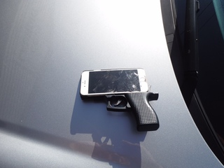 Gun-shaped cell phone case pointed at police