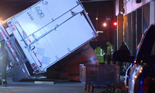 Semi-trailer hauling glass flips over under I-76